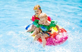A young boy and girl playing in a pool, splashing around on a swimming pool float. Young girl is wearing a pair of colorful goggles and both kids have swimming floaties on.