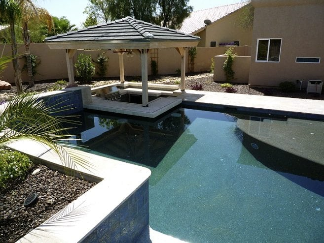 A view of a swimming pool with a gazebo connected to the swimming pool You can see a grill inside the gazebo for outdoor cooking.